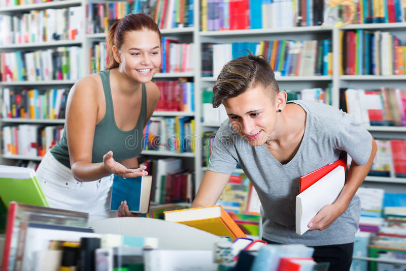 Portrait of girl and boy taking books stock photo