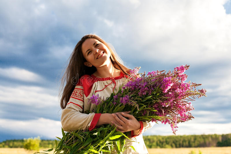 Portrait of a girl with a bunch of willow-herb in a green field royalty free stock photography