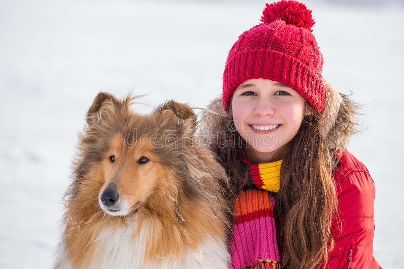 Portrait of girl with collie dog on snow field stock photos
