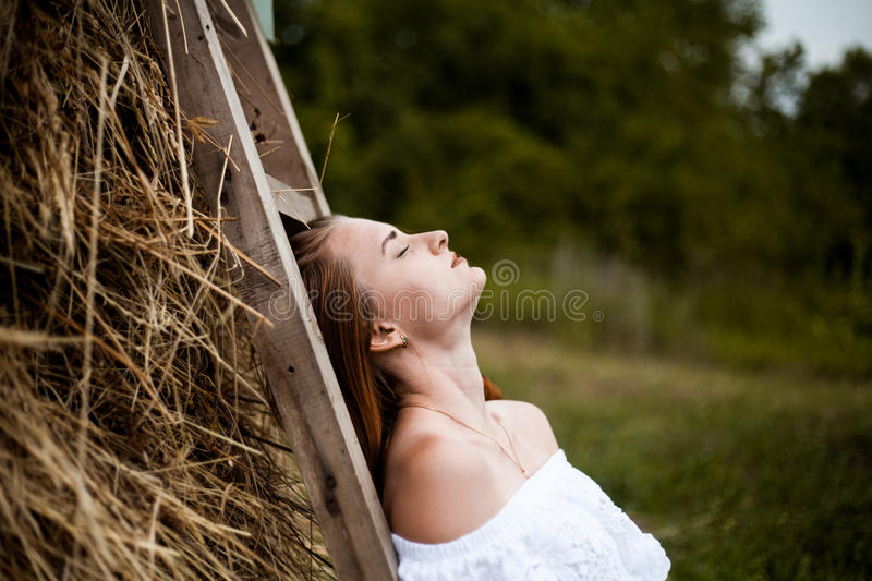 Portrait of a girl in a countryside. Relaxed, closed eyes, white dress stock photo