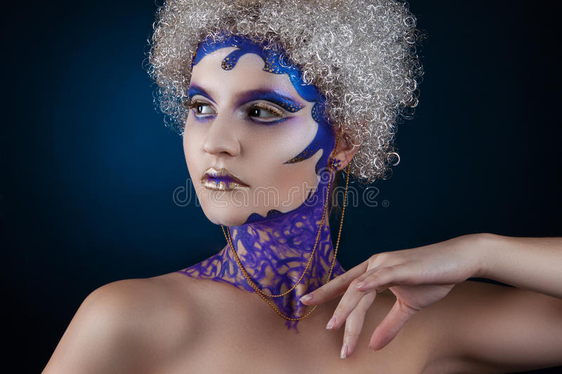 Portrait of a girl with creative make-up on a dark blue background. Purple - Gold Makeup. Winter portrait of a girl with creative make-up on a dark blue stock images