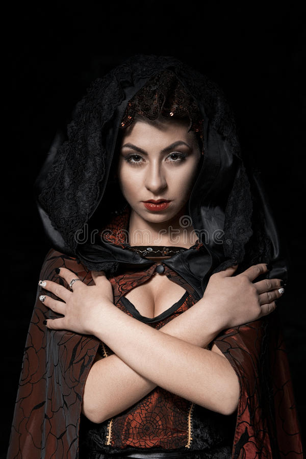 Portrait of a girl dark of the Queen with a crown on her head and make-up isolated on dark background, boobs beauty face. Portrait of a girl dark of the Queen stock image