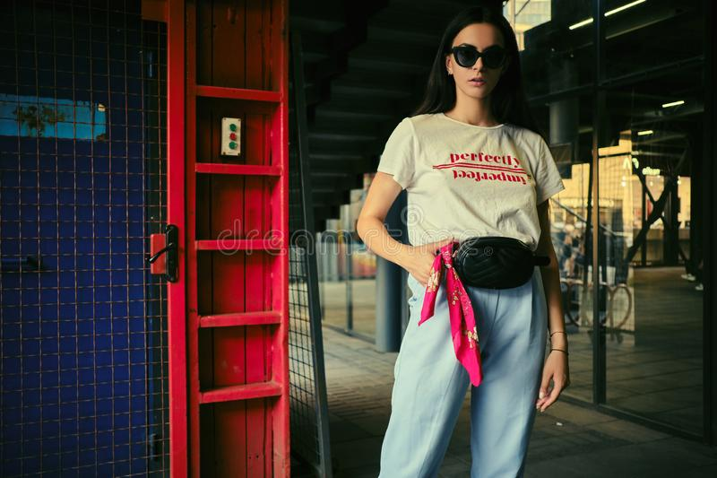 Portrait of a girl in dark sunglasses posing at a blue gate near the mall. Dressed in white t-shirt, blue trousers. Close-up portrait of a charming young stock photo