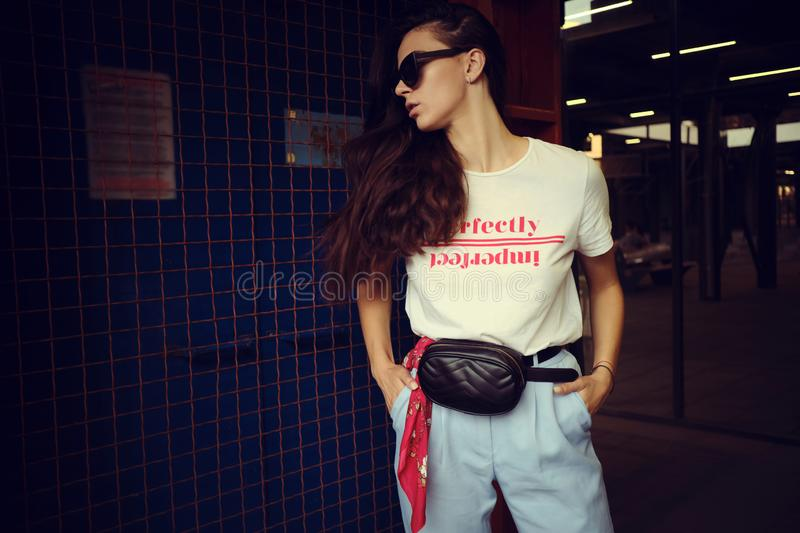 Portrait of a girl in dark sunglasses posing at a blue gate near the mall. Dressed in white t-shirt, blue trousers. Close-up portrait of an attractive young stock photo