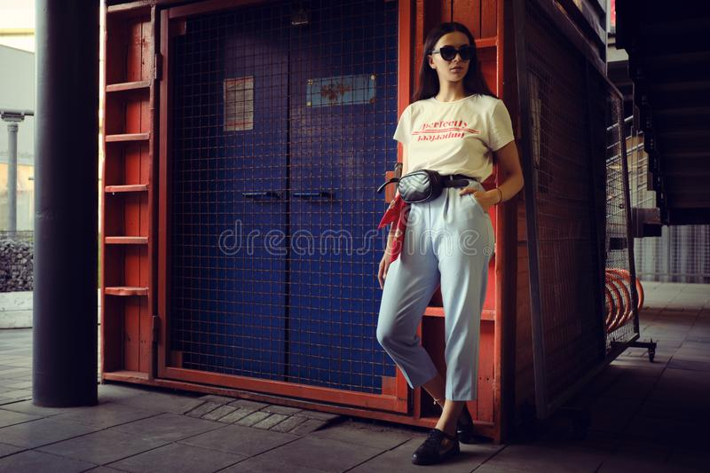 Portrait of a girl in dark sunglasses posing at a blue gate near the mall. Dressed in white t-shirt, blue trousers. Full length portrait of a charming young stock photo