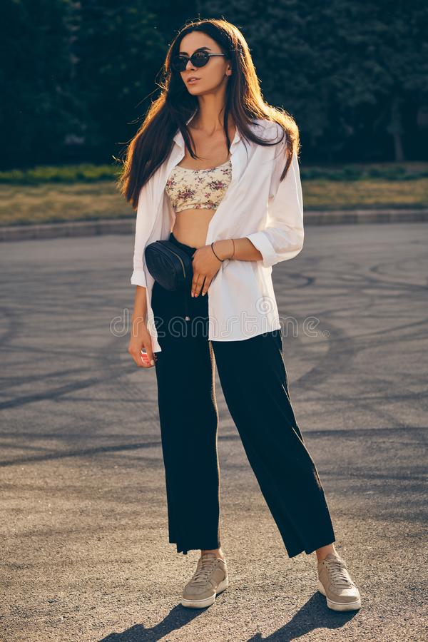 Portrait of a girl in dark sunglasses posing in city. Dressed in top with floral print, white shirt, black trousers stock photo