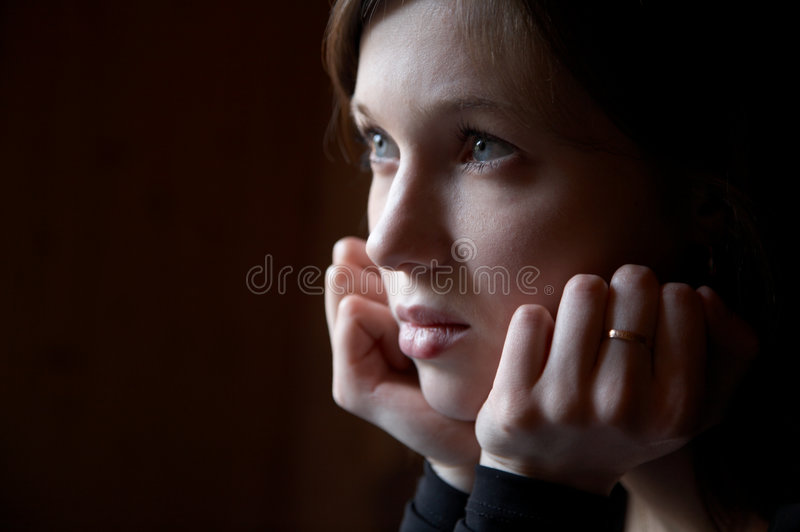 Portrait of the girl in a dark tonality. On a dark background stock image
