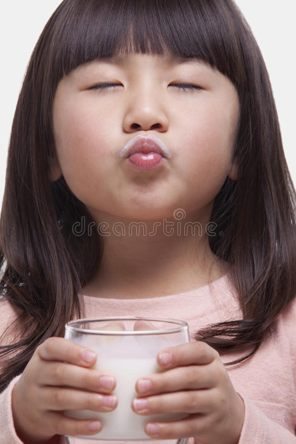 Portrait of girl drinking a glass of milk, making a face royalty free stock image