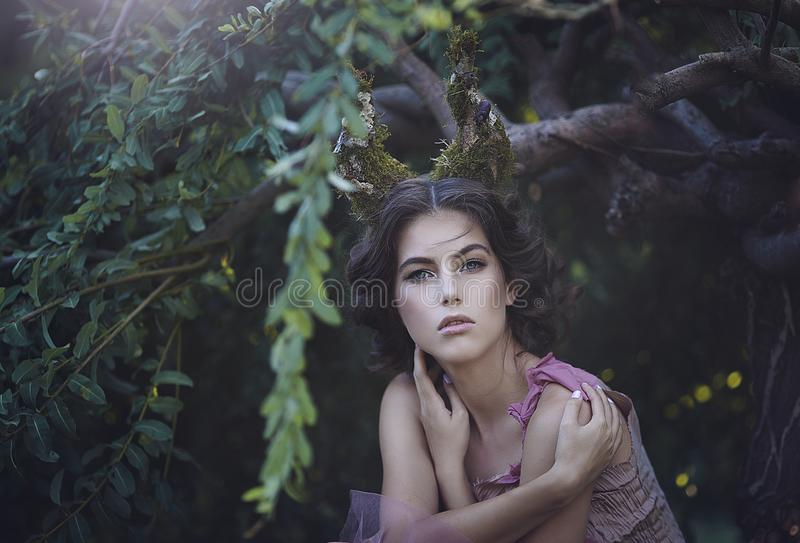 Portrait of girl enchanted Princess with horns. Girl Mystical creature fawn in shabby clothes in a fairy forest royalty free stock photography