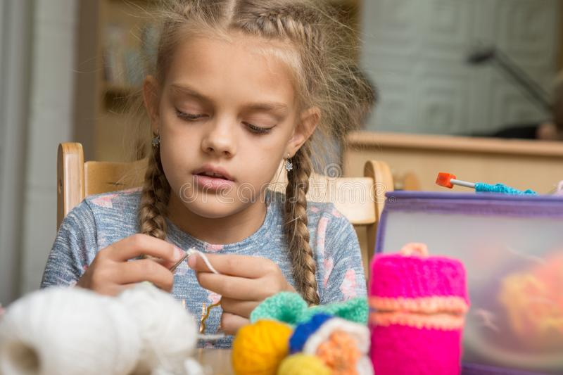 Portrait of girl enthusiastically engaged in knitting stock photos