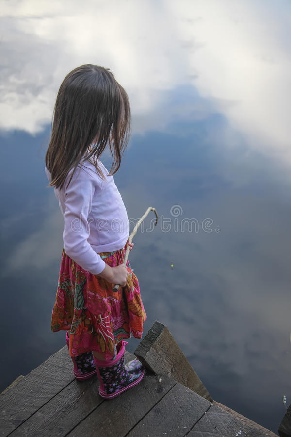 Portrait of a girl fishing in lake reflecting the sky royalty free stock photography