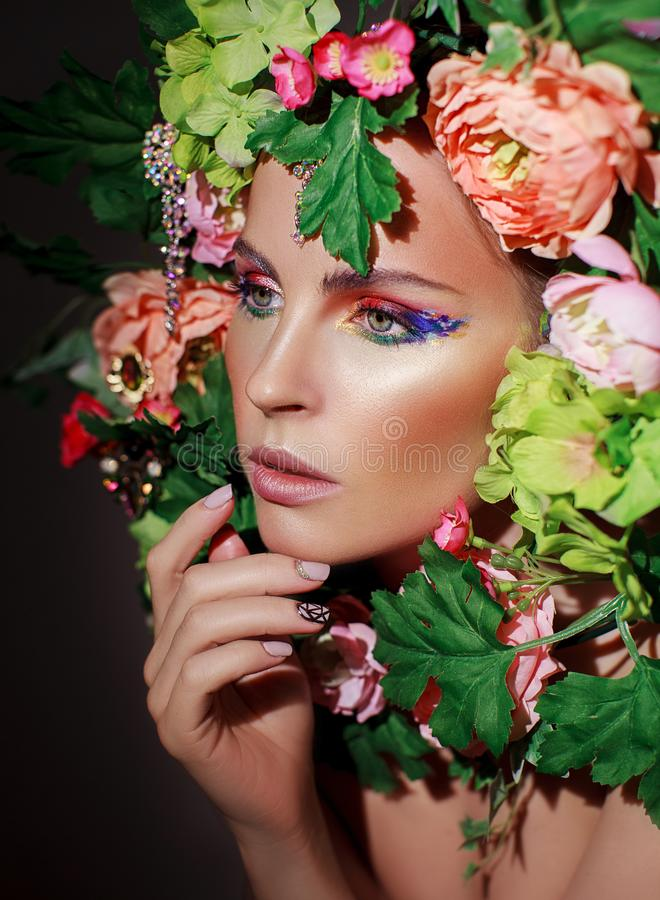 Portrait of a girl in flowers. Portrait of beautiful girl in flowers and leaves on black background. Multi-colored eye makeup royalty free stock photography