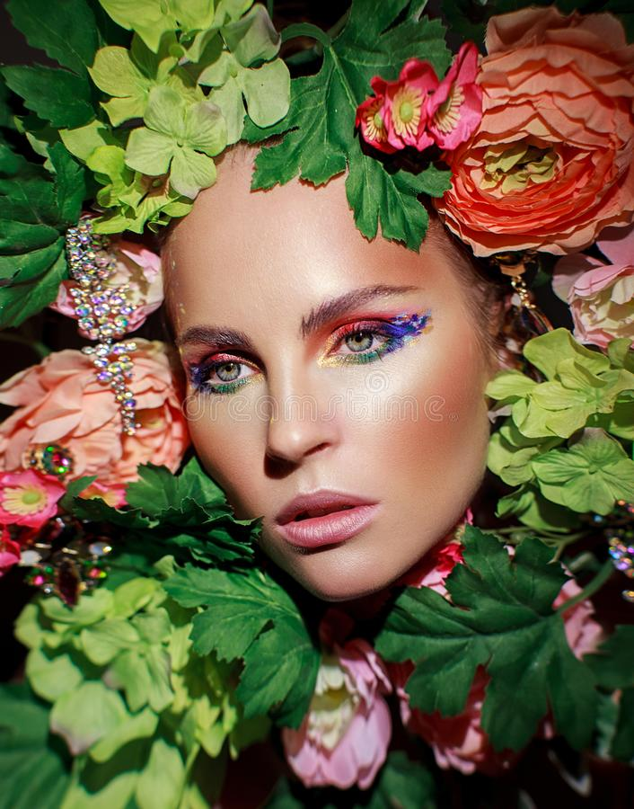 Portrait of a girl in flowers. Portrait of beautiful girl in flowers and leaves on black background. Multi-colored eye makeup stock photography