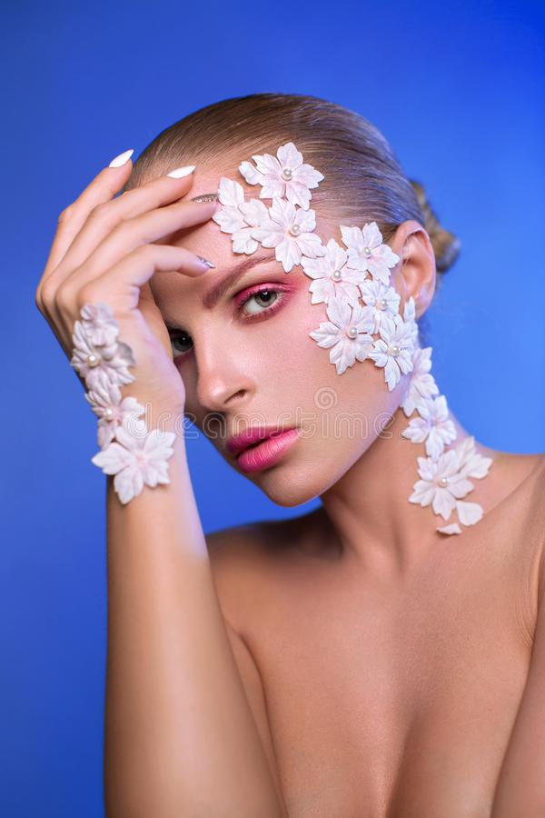 Portrait of a girl with flowers on her face stock photos