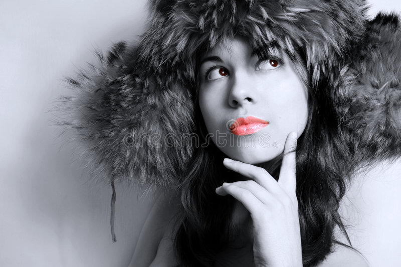 Portrait of the girl in a fur cap. It is black - a white portrait of the beautiful girl in a fur cap close up royalty free stock image