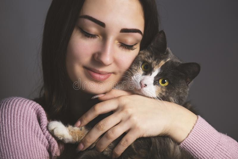Portrait of a girl gently pressed her cheek to cat, the girl with her eyes closed hugs the kitten on a gray background, the. Portrait of a girl gently pressed stock images