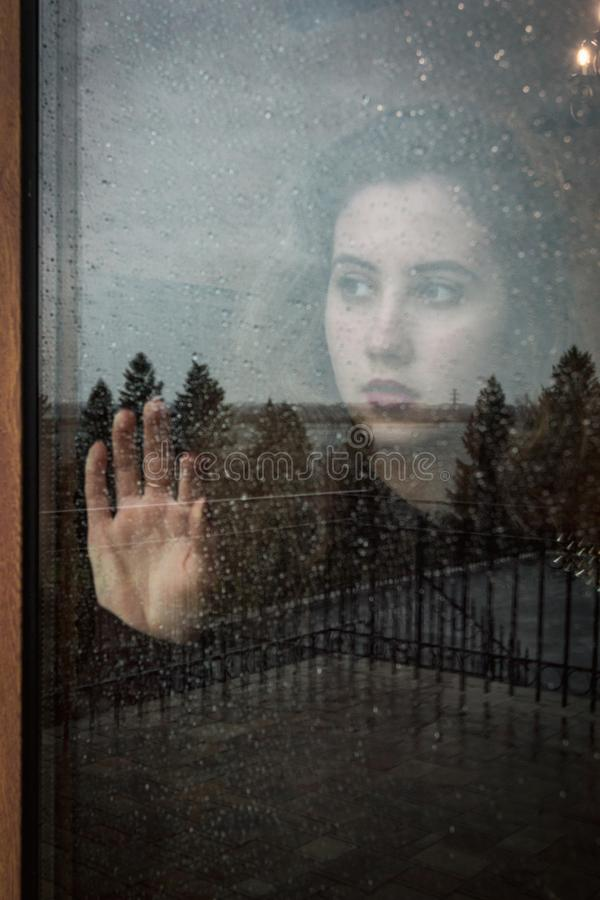 Portrait of a girl through a glass close-up in cloudy weather. Many drops of water royalty free stock image