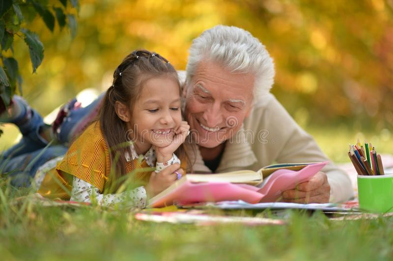 Girl and grandfather doing homework royalty free stock photos