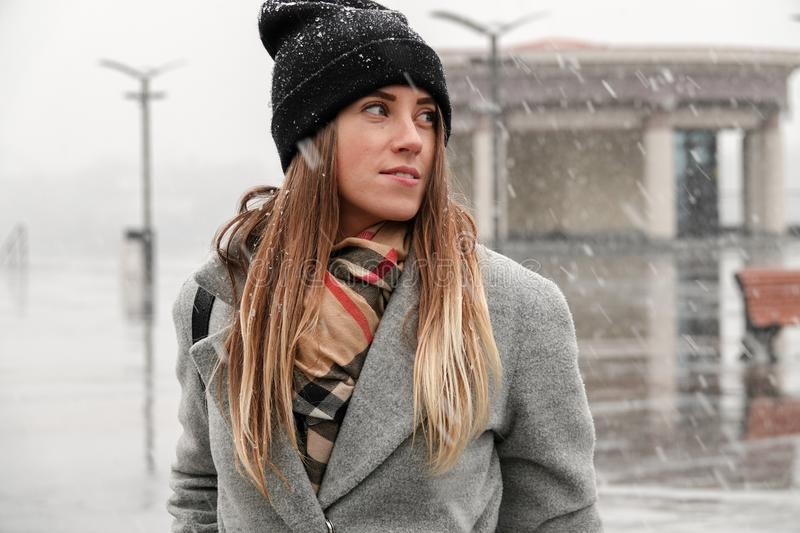 Portrait of a girl in a hat and a gray coat. royalty free stock photography