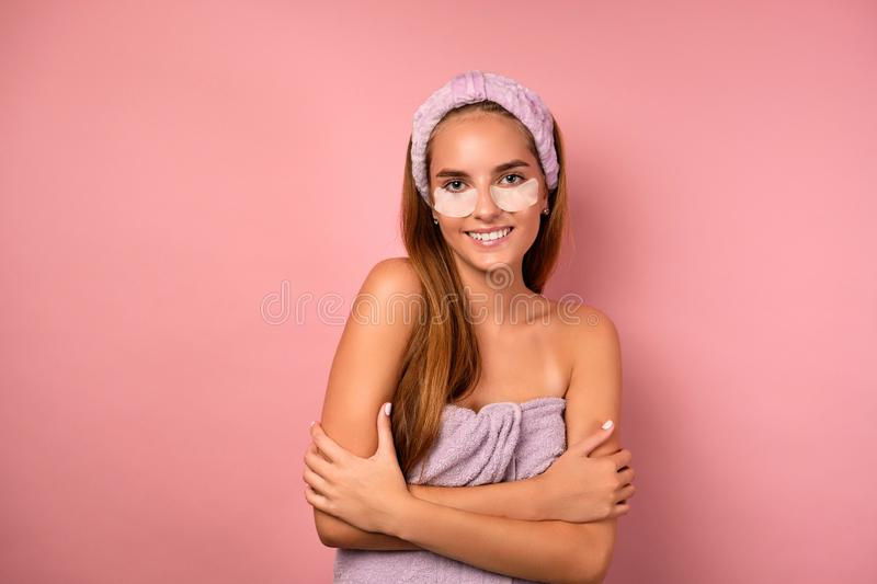 Portrait of a girl with her hair in a towel and patches under her eyes, hugging herself with hands on a pink background. stock images