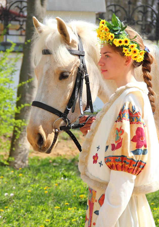 Portrait of a girl and her horse. Portrait of a girl in traditional Slavic dress with a wreath on his head with a beautiful white horse royalty free stock photography