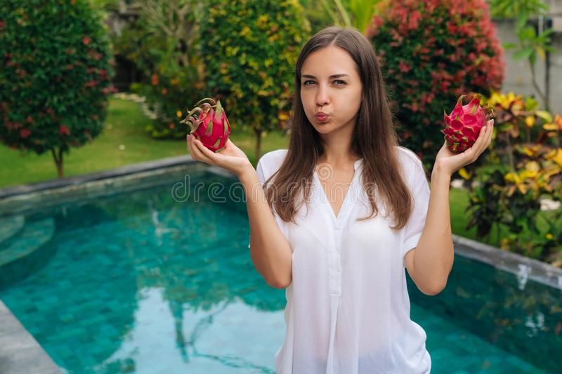 Portrait girl holds two dragon fruits, pitaya in her hands and makes funny face inflates her cheeks royalty free stock images