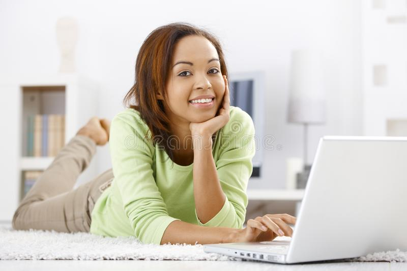 Portrait of girl at home with laptop. Portrait of girl lying on floor at home using laptop computer, browsing Internet, smiling at camera royalty free stock image
