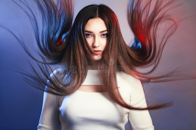 Portrait of girl with long hair flying in air on studio background, young woman looking straight confidently , fashion model, stock photo