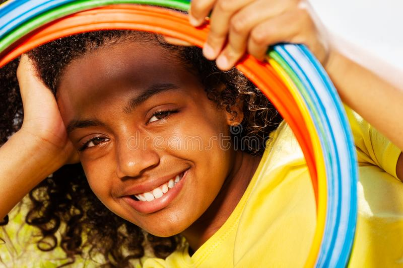 Portrait of girl look through color hoops smiling. Portrait of beautiful smiling young black mixed-race girl looking through color hoops rings royalty free stock photography