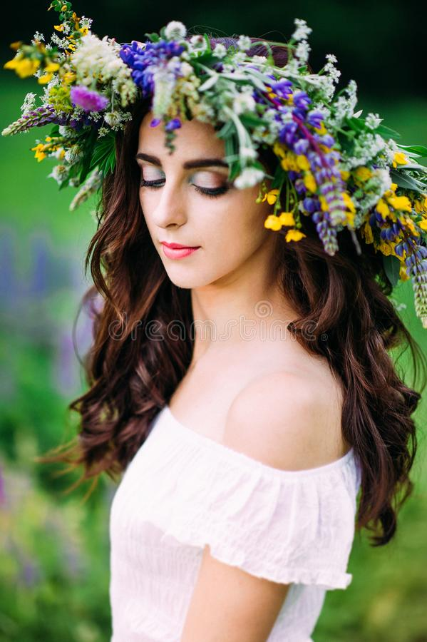 Portrait of girl looking down with wreath on head stock image