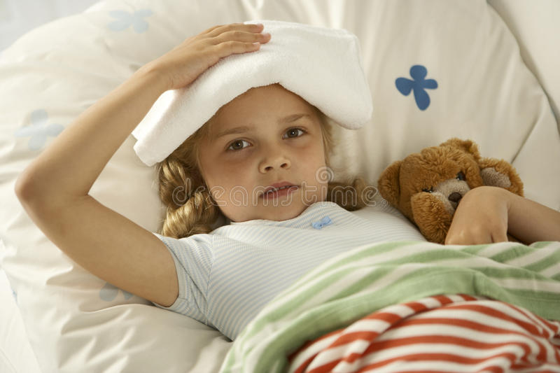 Portrait of a girl lying on the bed and holding a towel on her head stock photos