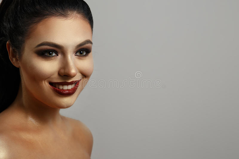 Portrait of a girl with makeup. beautiful smile. mask for the face. long black hair. gray background. nice smile royalty free stock photography