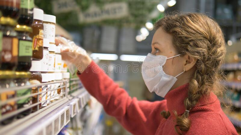 Portrait of girl in mask and gloves reads label on products in supermarket, personal protection coronavirus. Portrait of beautiful young girl in medical mask and royalty free stock image
