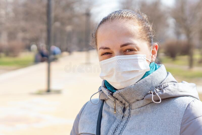 Portrait of a girl in a medical protective mask on her face, Covid-19 coronavirus pandemic, virus protection.  stock images