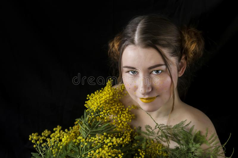 Portrait of a girl with mimosa close-up. Portrait of a young, beautiful woman with a bouquet of yellow, spring mimosa on a black background close-up stock images