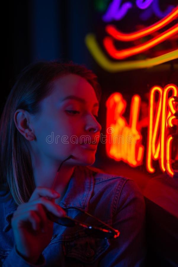 Portrait of a girl in neon lighting with glasses. Creative light, Vertical photo stock image