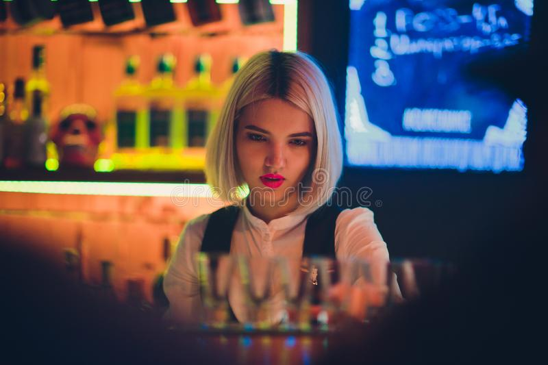 Portrait of a girl in a night bar, behind the counter. royalty free stock image