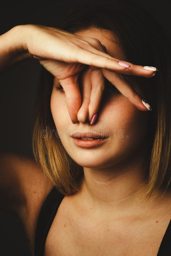 Free Portrait Girl On A Black Background, Clip.pinch Your Nose With Your Fingers. The Concept Of Bad Smell, Bad Air Ecology Royalty Free Stock Images - 164144629