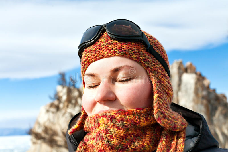 Portrait of a girl in orange scarves and hats against the blue s royalty free stock image