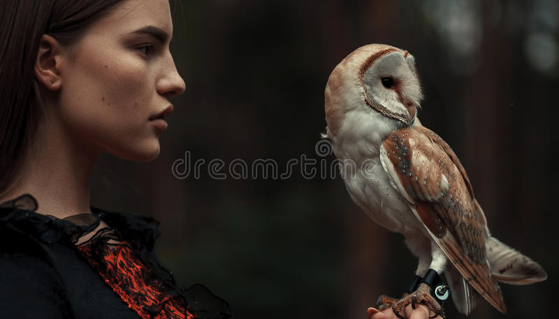 Portrait of girl with owl in hand. Close-up. royalty free stock photos