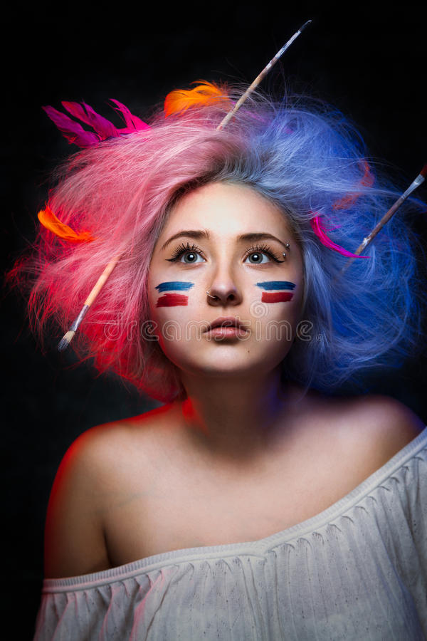Portrait of the girl painter with color paint on face with tattoo on hand and brushes for drawing in the hair. Artist with colored disheveled hair stock images