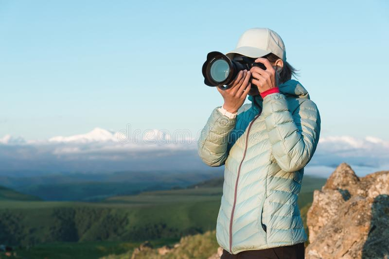 Portrait of a girl photographer in a cap on nature photographing on her digital mirror camera. Front view.  royalty free stock photography