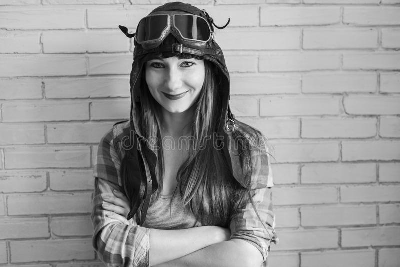 Portrait of a girl in pilot`s cap and glasses on a brick wall background, black and white photo royalty free stock images