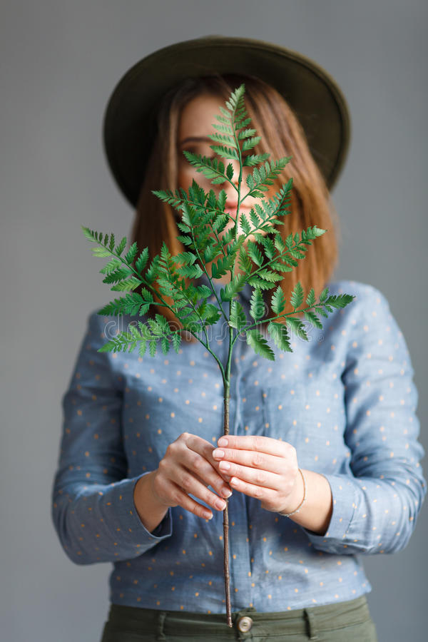Portrait of girl with a plant in hands royalty free stock photos