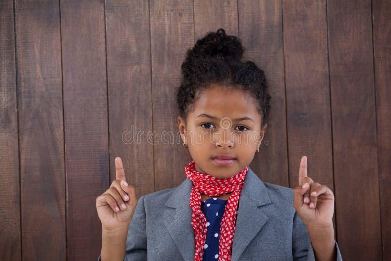 Portrait of girl pretending as businesswoman pointing upwards stock photos