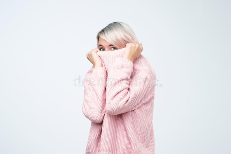Portrait of girl pulling her pink sweater over head. Woman with scared look disappearing in her clothes royalty free stock photos
