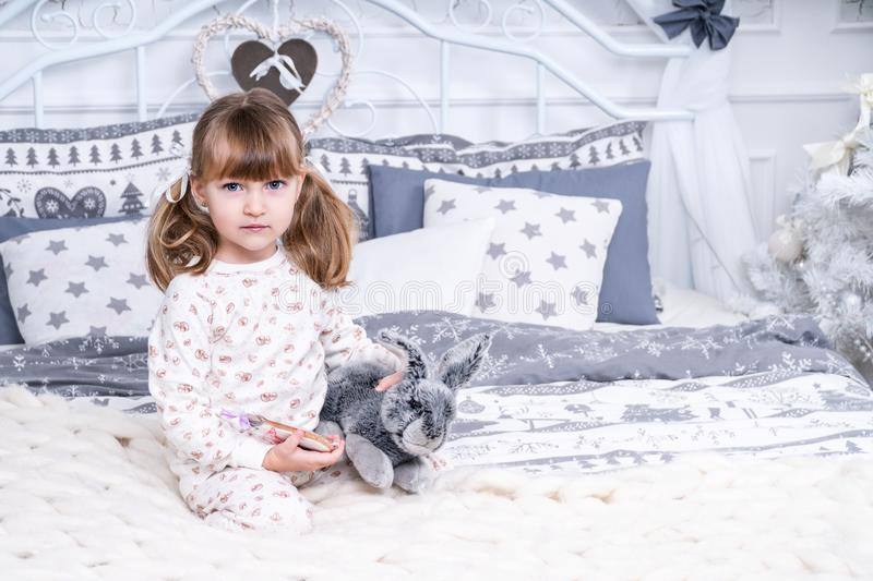 Portrait of girl with rabbit in bed royalty free stock images