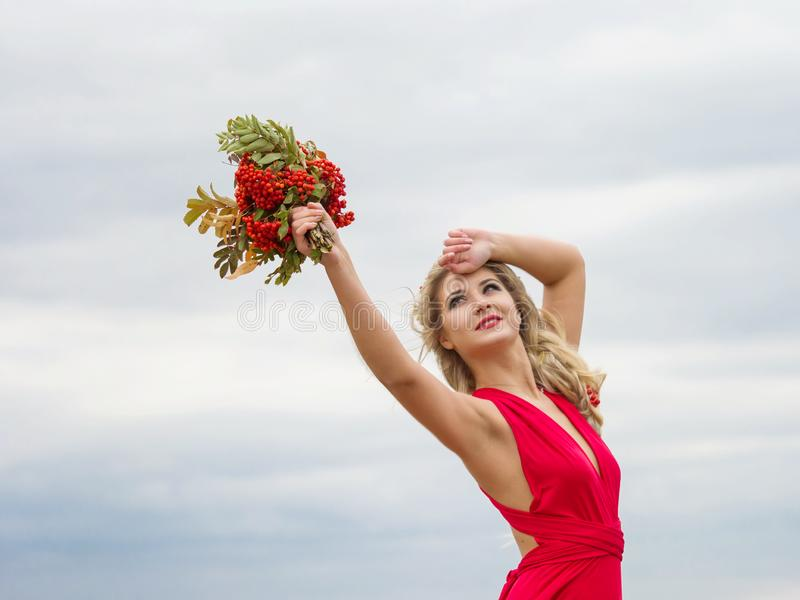 Portrait of a girl in a red dress pulling her arms up on a background of blue sky. Liberty. Autumn girl. Young woman in a red dress with a bouquet of mountain stock photos