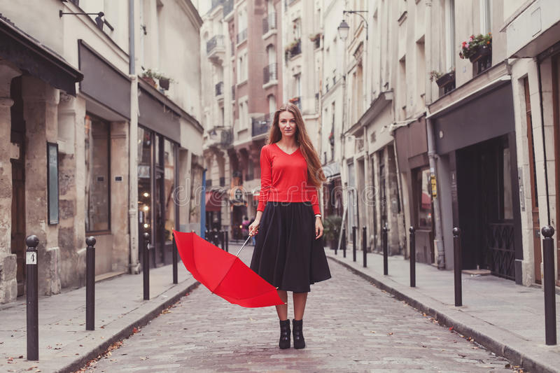 Portrait of girl with red umbrella in Paris. Beautiful woman, portrait of girl with red umbrella standing on the street of Paris stock images