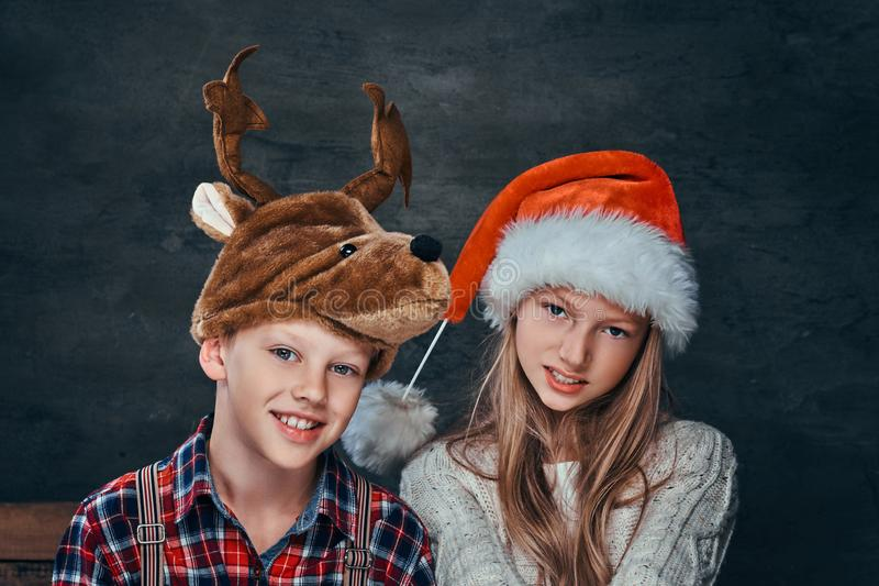 Portrait of a girl in Santa`s hat and boy in deer hat, smiling and looking at the camera stock photos